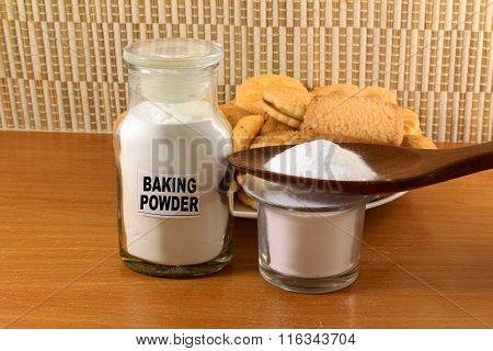baking powder in a glass jar and wooden spoon with cookie
