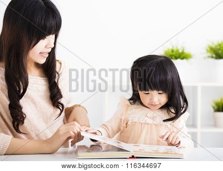 Mother  Helping Child Daughter To Reading