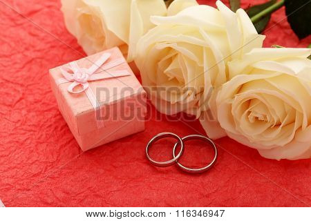 Silver Wedding Rings On A Red Paper Background