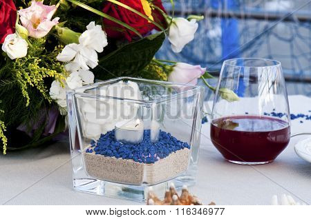 Particular Table Set By The Sea With Glass Of Wine And Candle