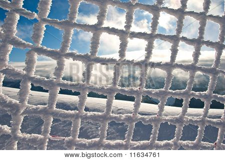 Frozen Mesh Fence With Blue Sky In Background