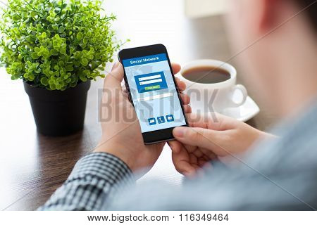 Man Holding Phone With Social Network On The Screen In Cafe