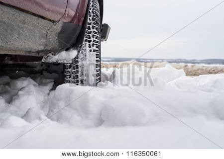 Car with mounted snow chains in wintry environment