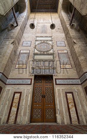 Cairo, Egypt - January 23, 2016: Old decorated wall with ornate wooden door in Al Rifaii Mosque, Cairo,  Egypt