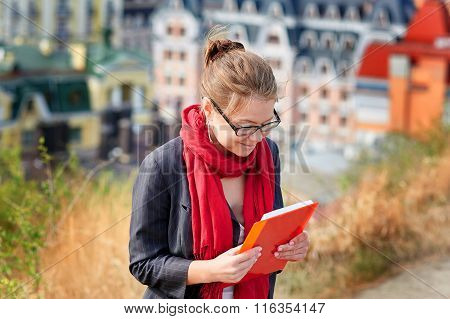Woman In Glasses With The Red Book On City Background