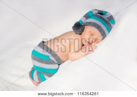 Newborn Baby Sleeps In A Knit Suit On A White Background