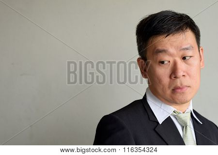 Mature Asian Executive Man looking from the corner of his eyes