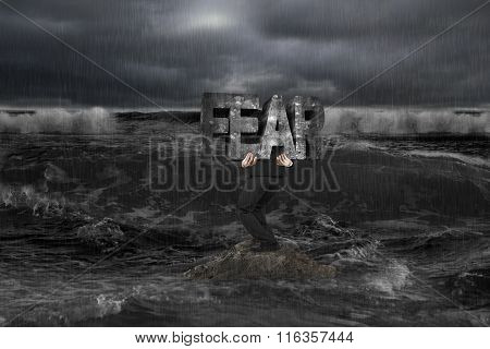 Businessman Carrying Old Structure Of Fear On Rock In Dark Ocean