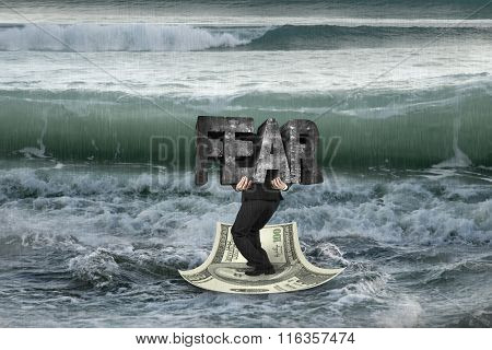 Businessman Carrying Fear On Money Boat In Ocean With Oncoming Waves