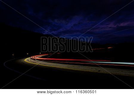 Light Of Cars Speeding In The Night Through Dence Curves In The Mountains