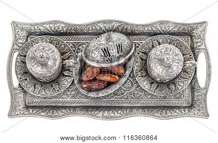 Table setting with silver tableware and dates. Oriental hospitality concept with tea or coffee cups. Top view