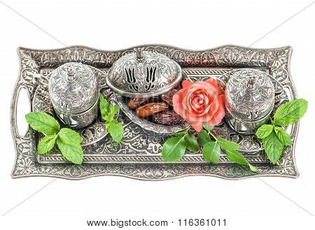Ta table setting with dates mint leaves and rose flower. Oriental hospitality concept