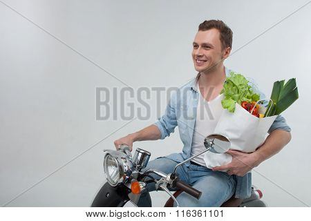Handsome guy with organic products on motorbike