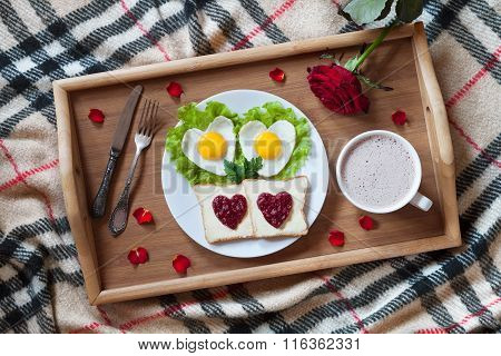 Breakfast in bed with heart-shaped eggs, toasts, jam, coffee, rose and petals. Valentines Day surpri