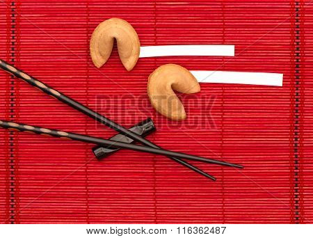Fortune cookies and black chopsticks on red bamboo mat. Chinese new years concept