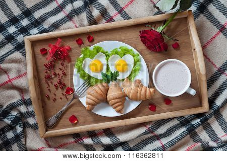 Romantic breakfast in bed with heart-shaped eggs, jam toasts, croissants, rose flower and petals