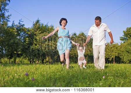 Family And Relationships Concepts. Happy Young Family Spending Time Together Outdoors On Nature