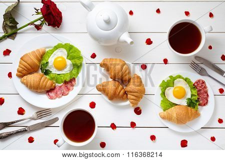 Breakfast for couple on Valentines day with heart shaped fried eggs, salad, croissants, salami sausa