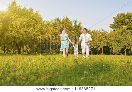 Family And Relationships Concepts. Happy Young Family Running Together Outdoors On Nature.