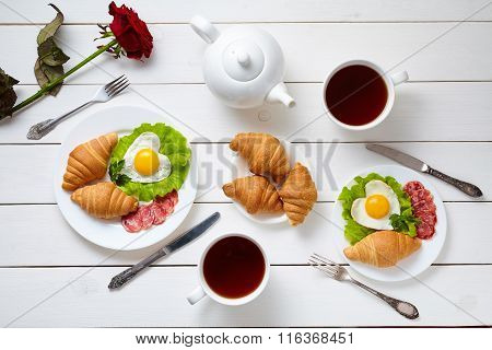 Heart shaped fried eggs, salad, croissants, salami sausage, rose flower composition and tea, white w