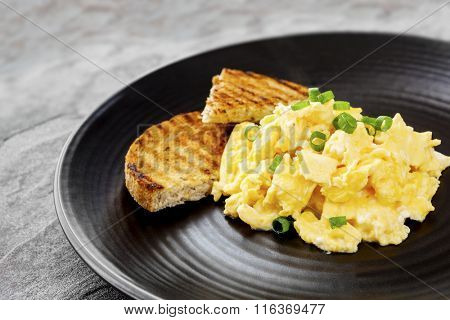 Scrambled eggs with toast on black plate.