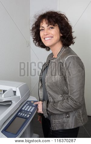 Side View Of A Woman Standing In Front Of Photocopier