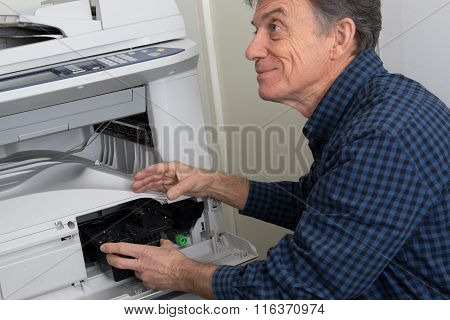 Side View Of Senior Man Fixing Cartridge In Photocopy Machine At Office