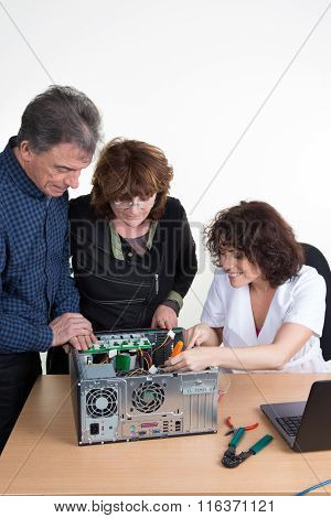 Technician Female Repairing A Computer And A Senior Couple