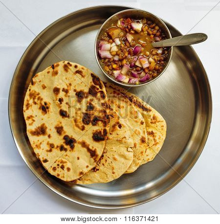 Indian tandoori roti with saboot masoor dal with raw onion toppings kept on a plain background