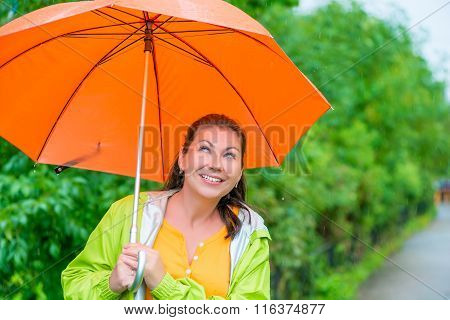 Portrait Of Happy Brunette Wearing A Raincoat Under An Orange Umbrella In The Rain