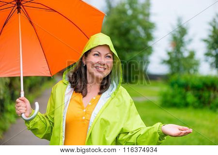Beautiful Girl In A Green Raincoat And With An Umbrella Under The Rain