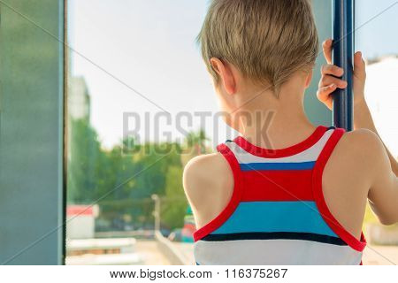 Boy In The Transport Looking Out The Window And Holding The Handrail
