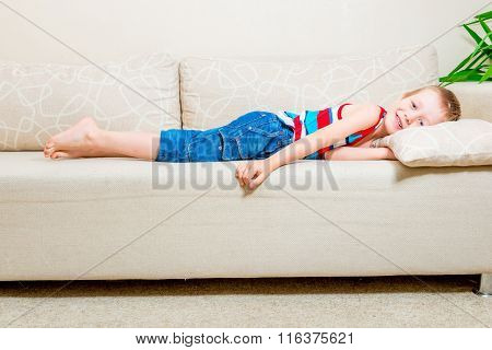 6 Years Old Boy Lying On The Couch In The Living Room