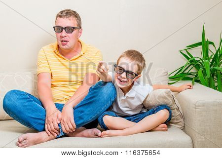 Father And Son Watching A Funny Movie On Tv In 3D Glasses