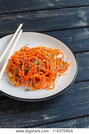 Spicy Pickled Carrot Salad In An Asian Style On A White Plate On A Dark Wooden Background. Vegan Foo