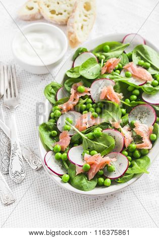 Fresh Salad With Green Peas, Spinach, Radish And Smoked Salmon On A Ceramic Plate On A Light Backgro