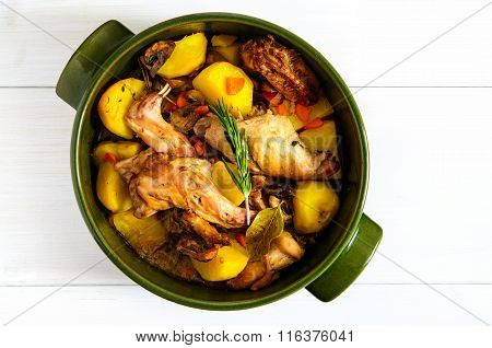 Top Flat View Of Roasted Rabbit Meat With Vegetables In Round Ceramic Pot On White Wooden Table Surf