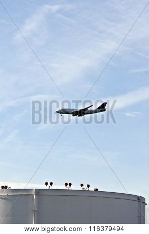 White Tanks In Tank Farm With Blue Sky And Approaching Aircraft