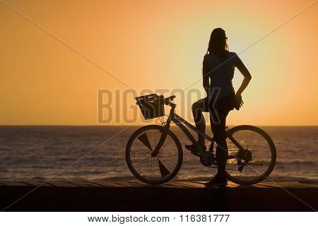 Silhouette of young woman cyclist on sunset