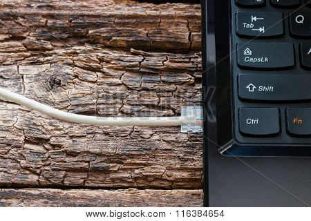 Notebook And Internet Cable On A Wooden Background