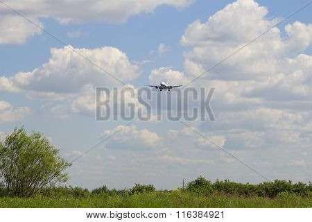 Summer landscape with coming in for a landing passenger plane