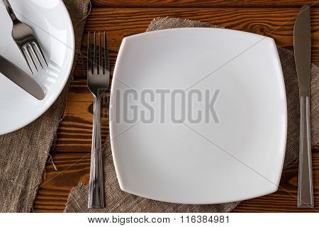 White Empty Plate With Cutlery On A Wooden Background