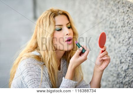 Young Blonde Woman Applying Lipstick Looking At Mirror In The Street