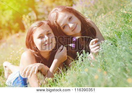 Two happy female friends playing in green grass