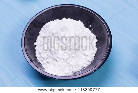 Bowl of potato starch on the wooden table