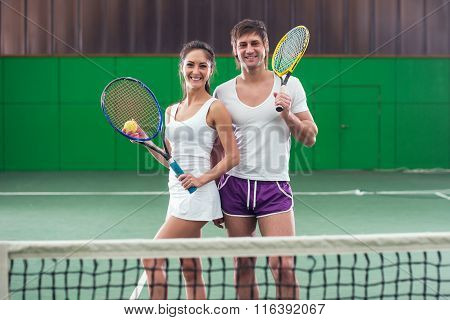 Tennis players portrait on court Smiling partners woman and man.