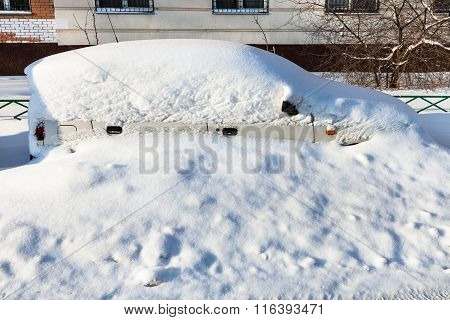 White Car Covered With Snow In Parking Lot