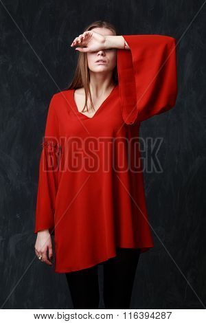 Portrait of a beautiful sad woman in red dressher eyes are closed by the hand dramatic pose