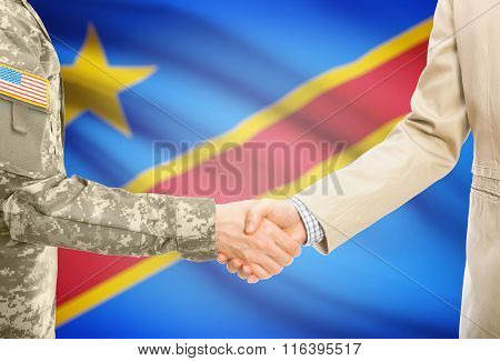 Usa Military Man In Uniform And Civil Man In Suit Shaking Hands With National Flag On Background - C