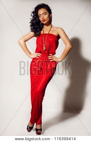 Gorgeous Woman With Dark Hair And Tanned Body, Wears Elegant Red Suit And Bijou